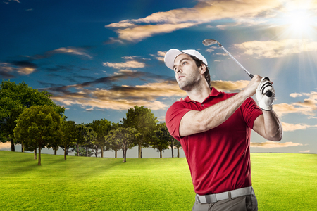 swing: Golf Player in a red shirt taking a swing, on a golf course. Stock Photo