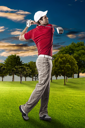 Golf Player in a red shirt taking a swing, on a golf course. Stock Photo