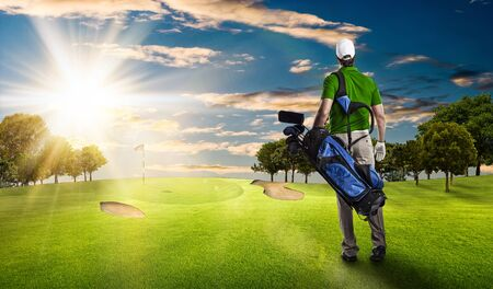 Golf Player in a green shirt walking with a bag of golf clubs on his back, on a golf course.