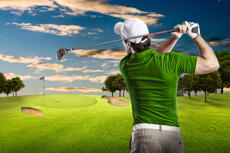 swing: Golf Player in a green shirt taking a swing, on a golf course.