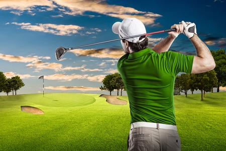 columpio: Jugador de golf en una camisa verde que toma un oscilaci�n, en un campo de golf. Foto de archivo