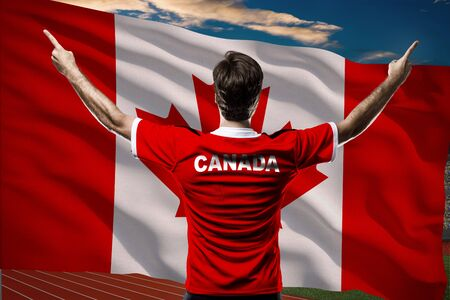 canadian football: Canadian Athlete in front of a Canadian flag.