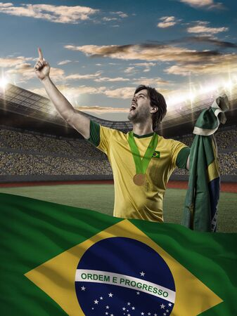 Brazilian Athlete Winning a golden medal with a brazilian flag in front. Stock Photo