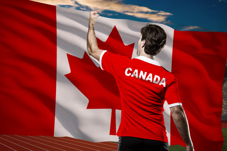 nationalistic: Canadian Athlete in front of a Canadian flag.