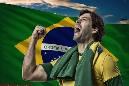 Brazilian Athlete in front of a brazilian flag.