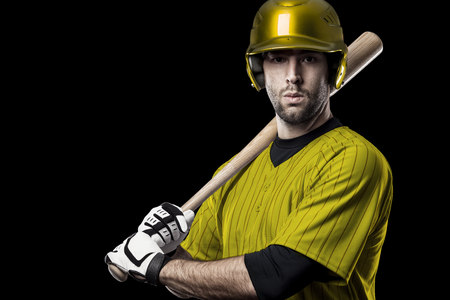 Baseball Player with a yellow uniform on a black background. Stock Photo
