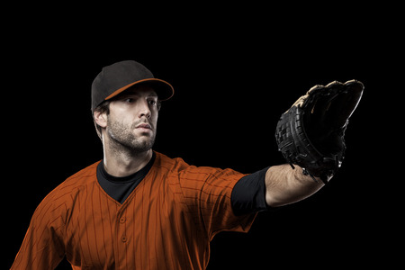 Baseball Player with a orange uniform on a black background. Stock Photo