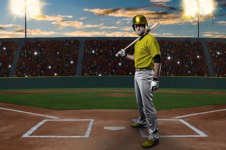 toughness: Baseball Player with a yellow uniform on baseball Stadium.