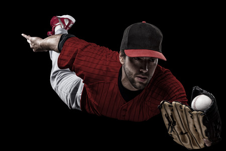 Baseball Player with a red uniform on a black background. Stock Photo