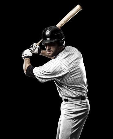 Baseball Player with a white uniform on a black background. Stock Photo