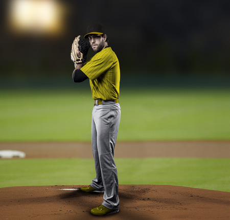 Pitcher Baseball Player with a yellow uniform on baseball Stadium.