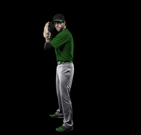 Pitcher Baseball Player with a green uniform on a black background. Stock Photo