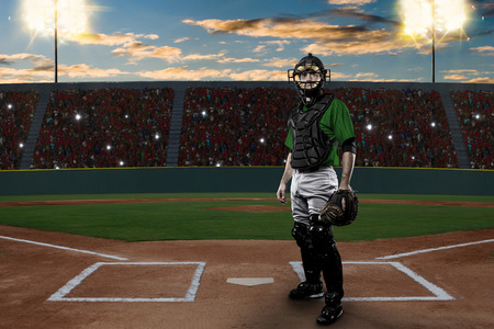 Catcher Baseball Player with a green uniform on a baseball Stadium.