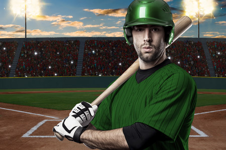 Baseball Player with a green uniform on baseball Stadium.
