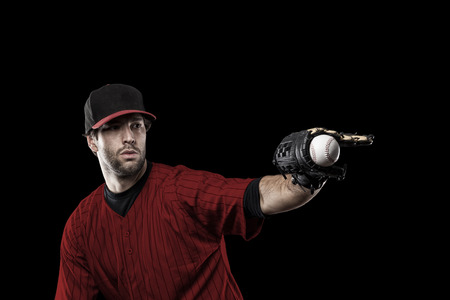 toughness: Baseball Player with a red uniform on a black background. Stock Photo