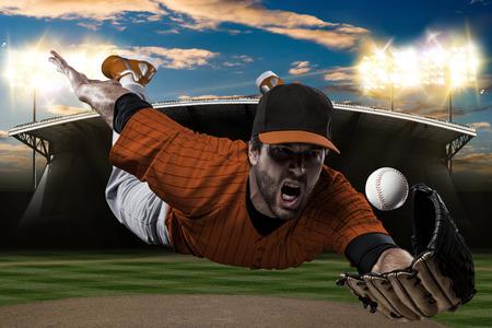 Baseball Player with a orange uniform on baseball Stadium. Stock Photo