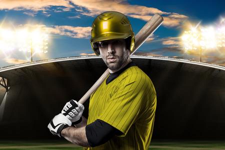 Baseball Player with a yellow uniform on baseball Stadium.