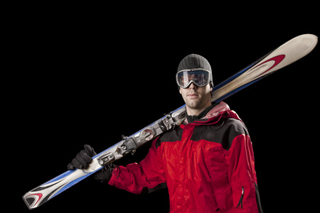 Skier with a red jacket, holding a pair of skis on a black background.. Stock Photo