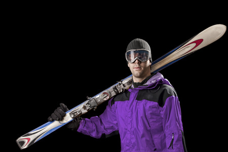 Skier with a purple jacket, holding a pair of skis on a black background.