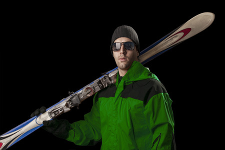 Skier with a green jacket, holding a pair of skis on a black background.