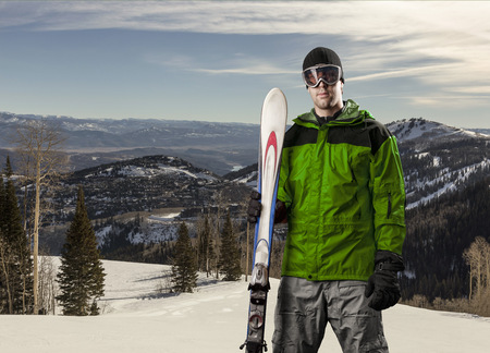Skier with a green jacket, holding a pair of skis on a snowy mountain.