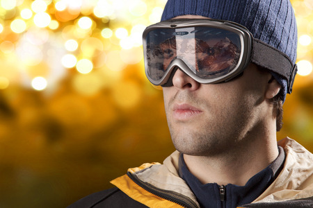 skier looking for a snowy mountain on a yellow lights background. Stock Photo