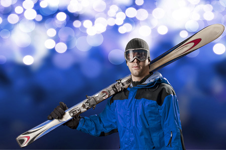 Skier with a blue jacket, holding a pair of skis on a blue lights background.
