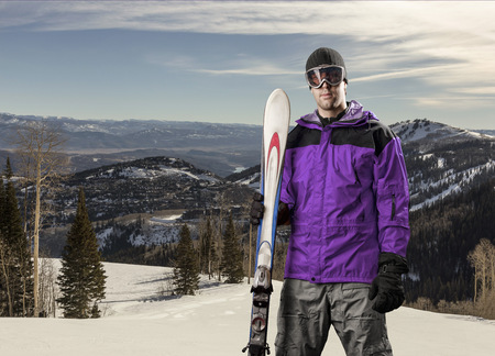 Skier with a purple jacket, holding a pair of skis on a snowy mountain.