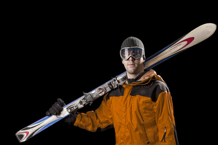 Skier with a orange jacket, holding a pair of skis on a black background.