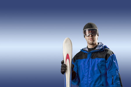Skier with a blue jacket, holding a pair of skis on a blue background.