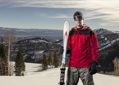 Skier with a red jacket, holding a pair of skis on a snowy mountain.