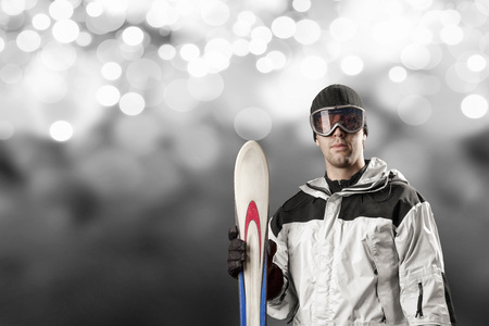 Skier with a white jacket, holding a pair of skis on a white lights background.