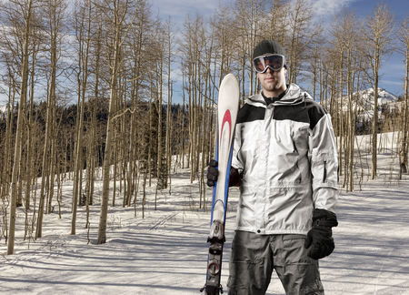 Skier with a white jacket, holding a pair of skis on a snowy mountain.