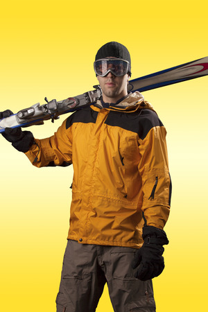 Skier with a yellow jacket, holding a pair of skis on a yellow background.