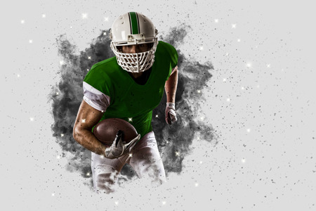 Football Player with a Green uniform coming out of a blast of smoke .