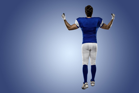 Football Player with a blue uniform walking, showing his back on a blue background. Stock Photo