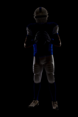 Silhouette of a football Player with a blue uniform on a black background.