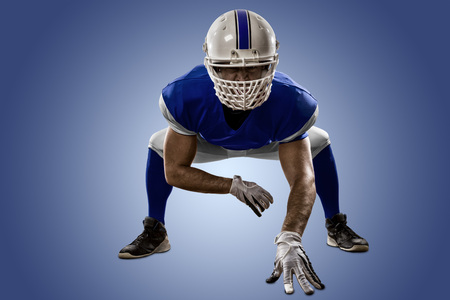 Football Player with a blue uniform on the scrimmage line, on a blue background. Stock Photo