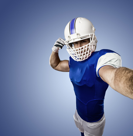 Football Player with a blue uniform making a selfie on a blue background.