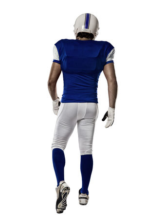 Football Player with a blue uniform walking, showing his back on a white background.