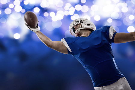 Football Player with a blue uniform making a catch on a blue lights background.