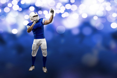 Football Player with a blue uniform making a selfie on a blue lights background. Stock Photo