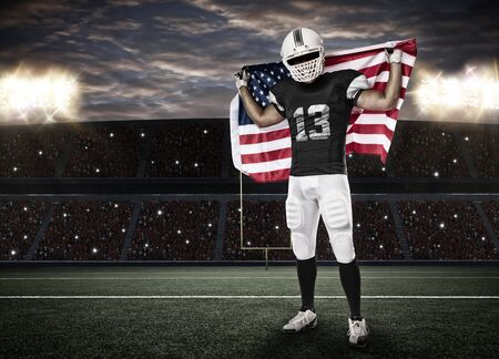 Football Player with a Black uniform and a american flag, on a stadium. Stock Photo