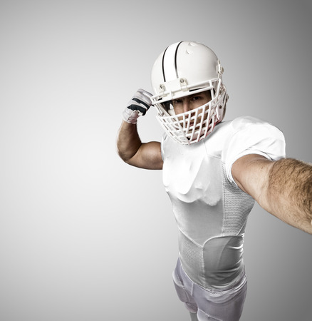 Football Player with a white uniform making a selfie on a white background.