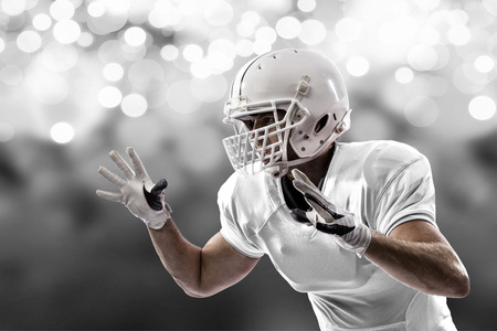 Football Player with a white uniform making a tackle on a white lights background.