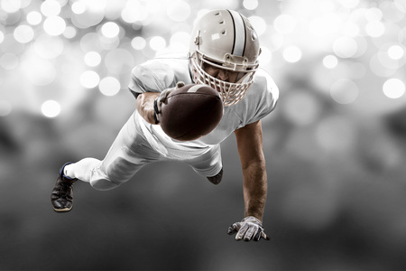 Football Player with a white uniform scoring on a white lights background.