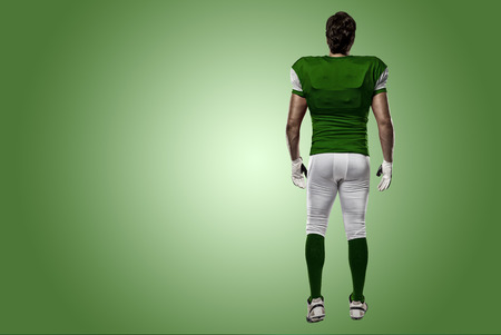 Football Player with a green uniform walking, showing his back on a green background. Stock Photo