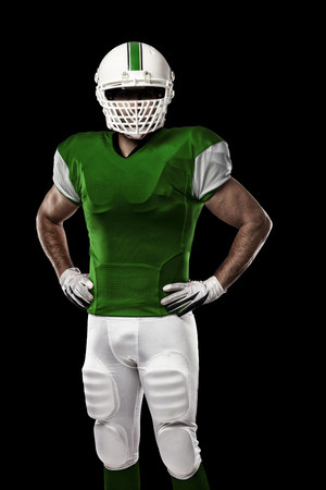 Football Player with a Green uniform on a black background. Stock Photo