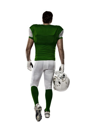 Football Player with a Green uniform walking, showing his back on a white background.