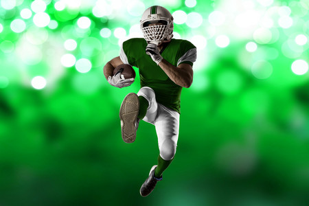 Football Player with a green uniform Running on a green lights background.